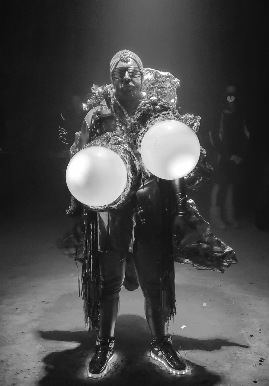 Black and white photograph of a person in an elaborate, shiny costume with two large glowing orbs