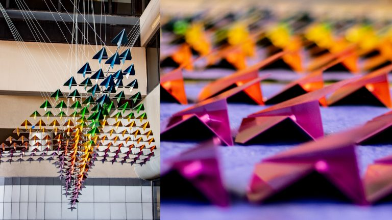 Two images: left image shows a large rainbow-colored metal sculpture of small paper airplanes that together form a large paper airplane; image two shows a close up of several small paper airplanes