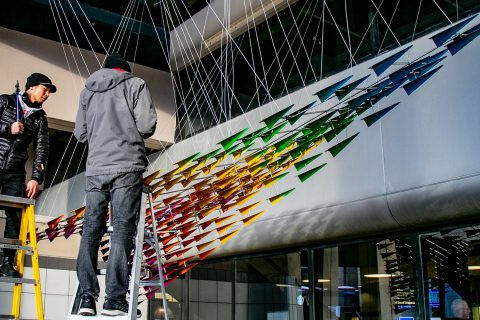 Image showing two people on ladders adding wiring to a large metal sculpture of rainbow-colored paper airplanes that together make up one large paper airplane