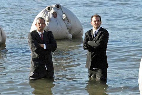 Photo of two men in suits sanding in knee-deep water with three figures in large inflated white fabric surrounding them.