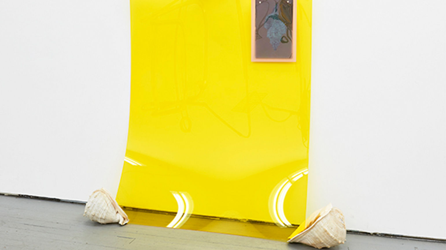 Image of artwork by Las Hermanas Iglesias, showing a large transparent yellow sheet leaning against a wall with conch shells.