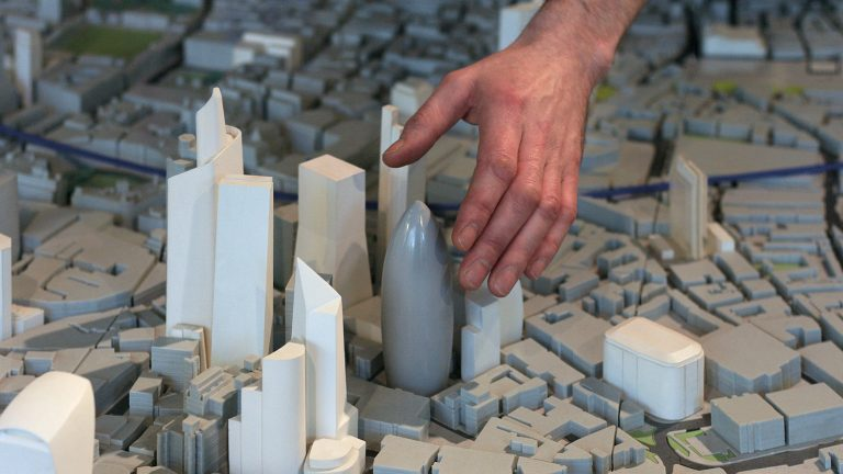 An image of a hand reaching down into a small-scale model city