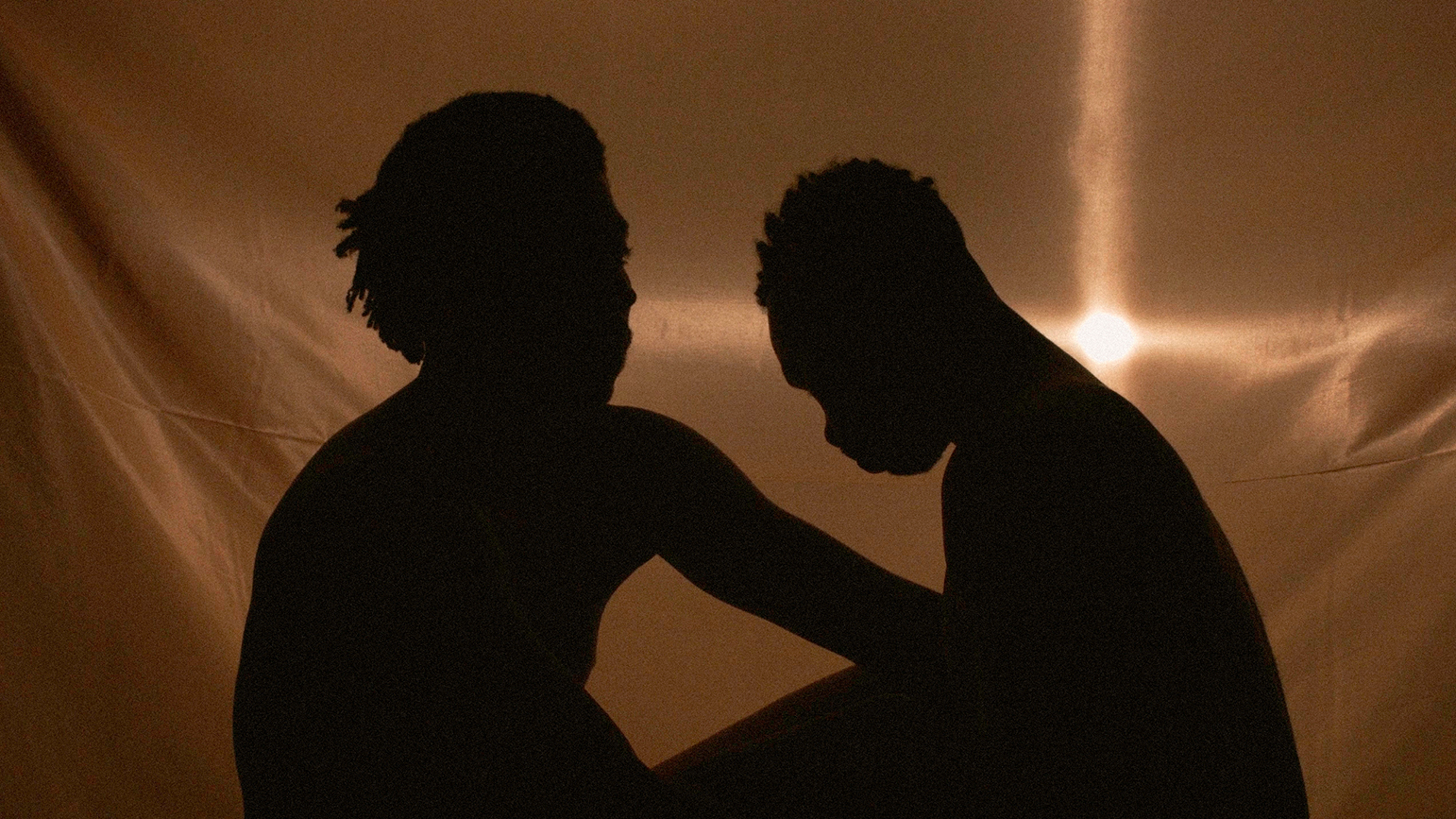 Image of two silhouettes sitting facing one another against a backlit gold cloth