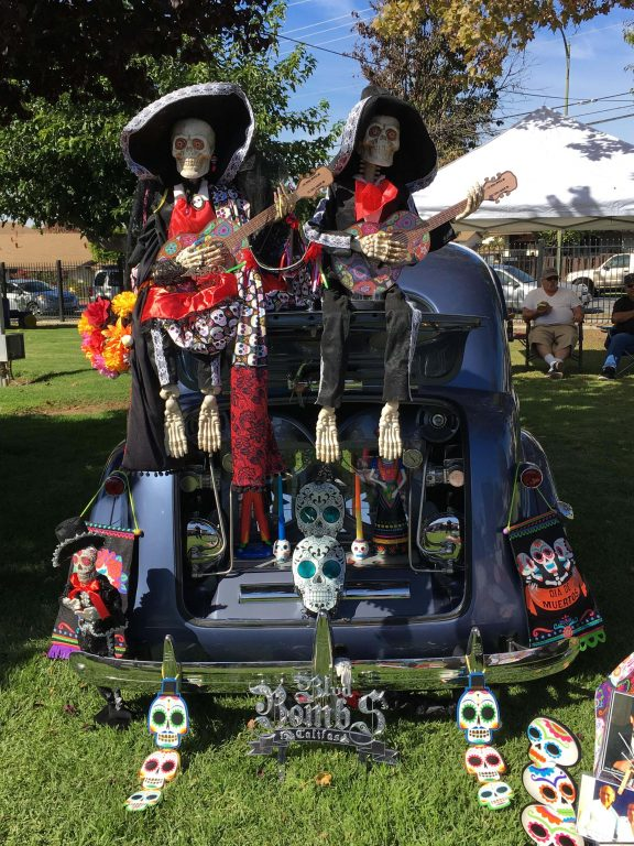 Two dressed skeletons playing painted guitars sit on top of an open truck filled with candles and stylized paper skulls