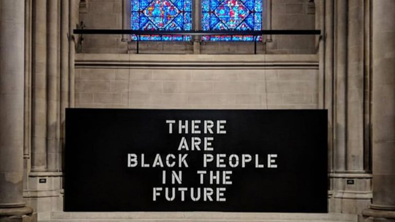 "Photograph of a black sign reading ""There are Black People in the Future"" installed under a stained glass window in a church"