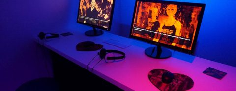 "Photograph showing two computers with images from Angela Washko's ""The Game: The Game"""