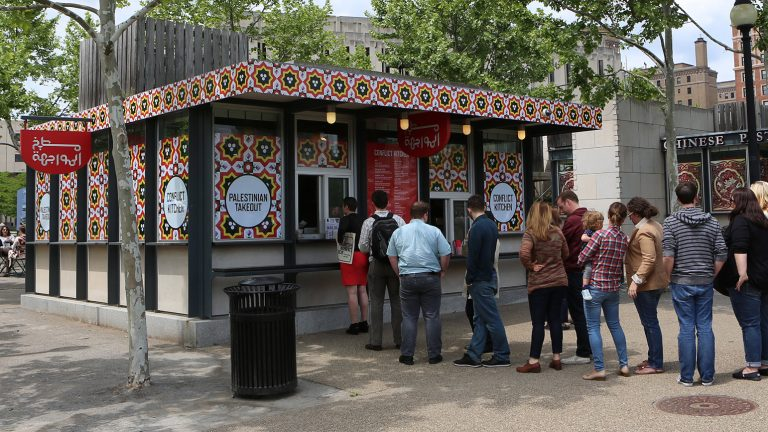 Photograph showing the exterior of the Palestinian version of Conflict Kitchen with a line of people