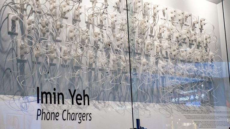 Photograph of an installation of hundreds iPhone chargers constructed from paper plugged into paper outlets