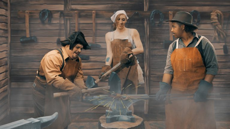 Video still showing three blacksmiths against a cartoonist background