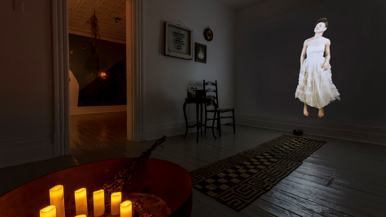 Image of an installation by Alisha Wormsley showing a projection of a woman, candles, and other domestic items