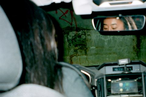 Photograph taken from the back seat of a car showing the reflection of the driver's eyes in the rear view mirror