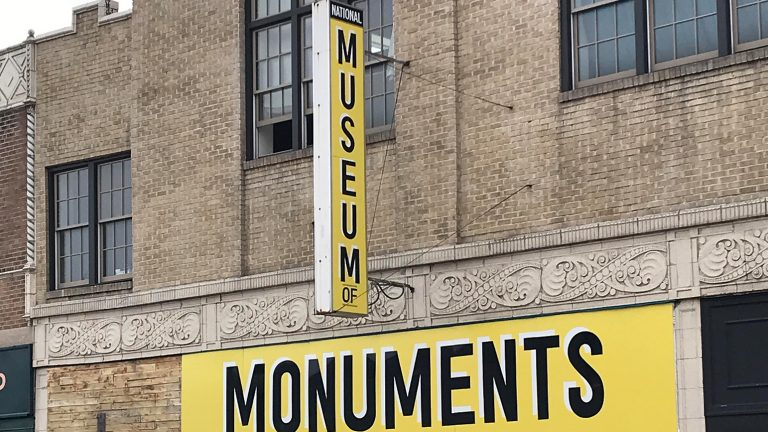 "Photograph of a store front with signage reading ""National Museum of"" and ""Monuments"""