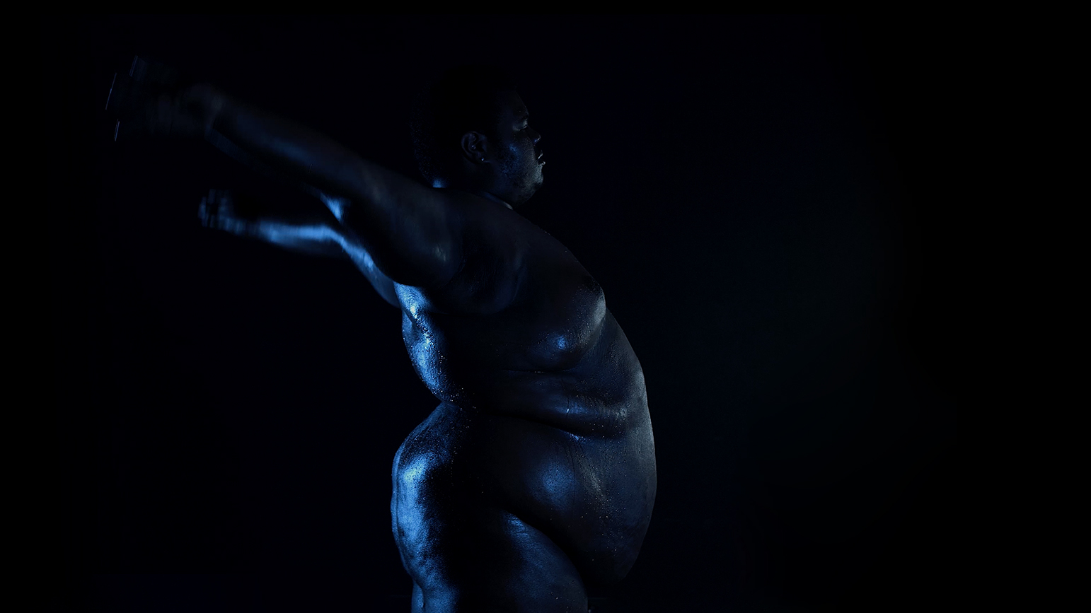 Video still of a nude figure in very low lighting from the side with arms reaching backward