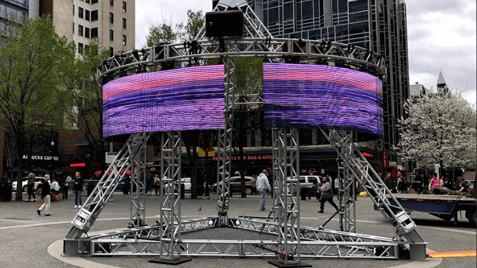 Image of circular video screens on a pyramid structure installed in a the middle of a public square