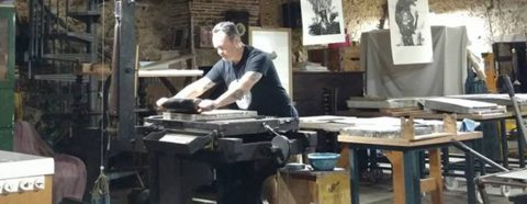 Photograph of a person at a printing press