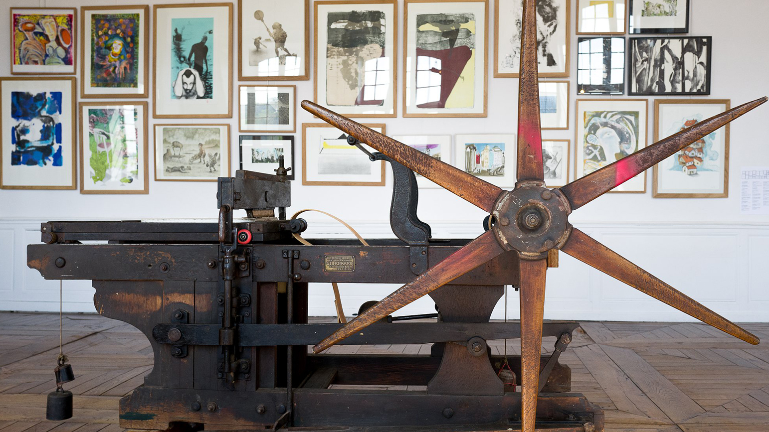 Photograph of a manual printing press with framed prints hung salon-style behind it.