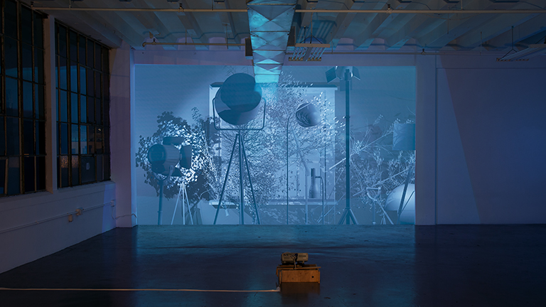 Blue projection in a dark room with geometric digitally-created forms