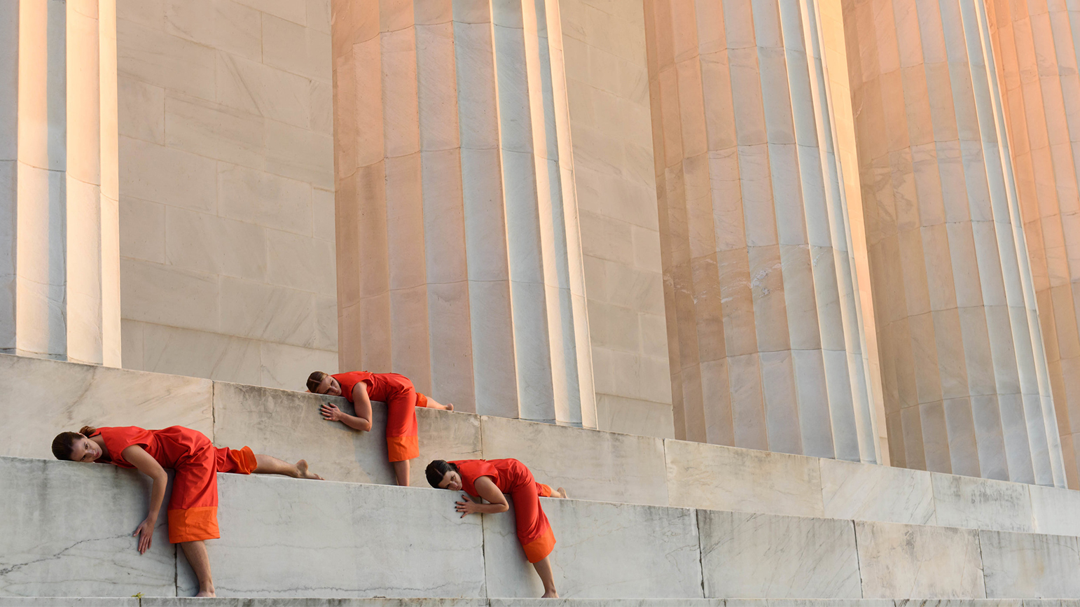 Women in orange jumpers lying on steps in front of a colonnade