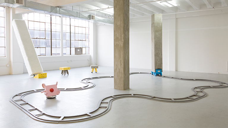 Train tracks set up in a white gallery with a blue car with a column on top of it