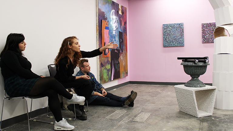 Seated woman talking and pointing to sculptures in front of her; two other figures sit on either side and painting hang in the background