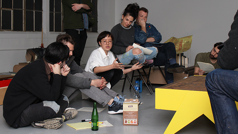 A group of people sitting on the floor and on chairs having a discussion