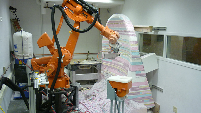 Large orange robot sculpting a multicolored foam block