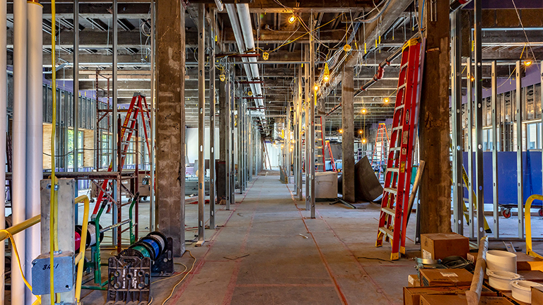 Large interior space under construction with exposed concrete floors and ceiling and metal framing