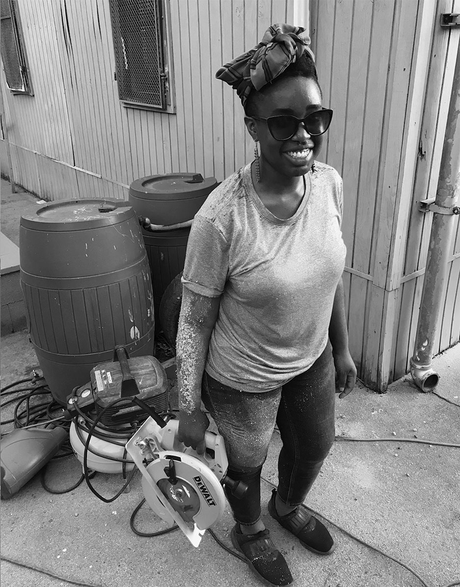 Black and white photograph of a woman holding a circular saw and smiling at the camera