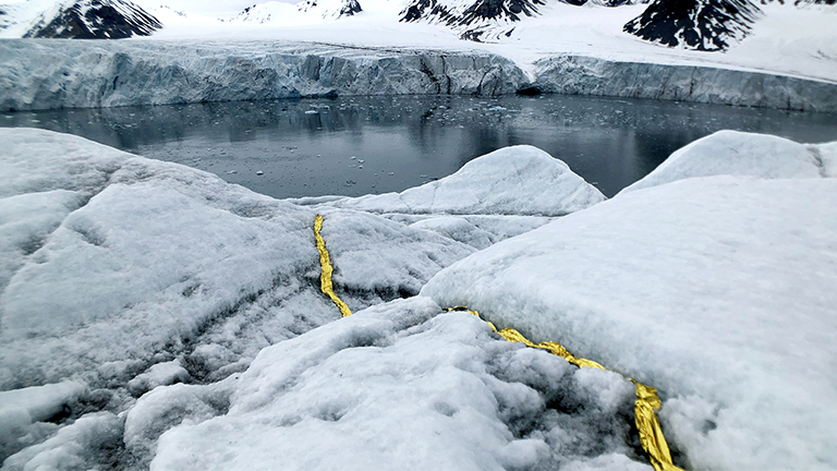 Gold emergency blankets placed inside the crack of a glacier