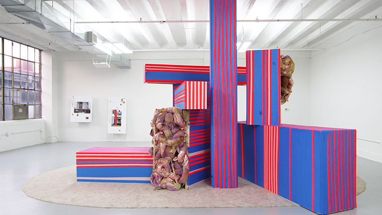 Large rectangular blue and red striped sculptures in a white gallery