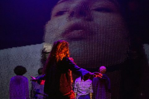 The stage saturated in purple. One dancer's hair covers her face with her arms out to the side, she stands in front of a close up pixelated projection of a white woman's face.