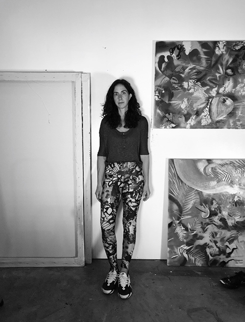 Black and white photograph of a woman standing next to abstract paintings