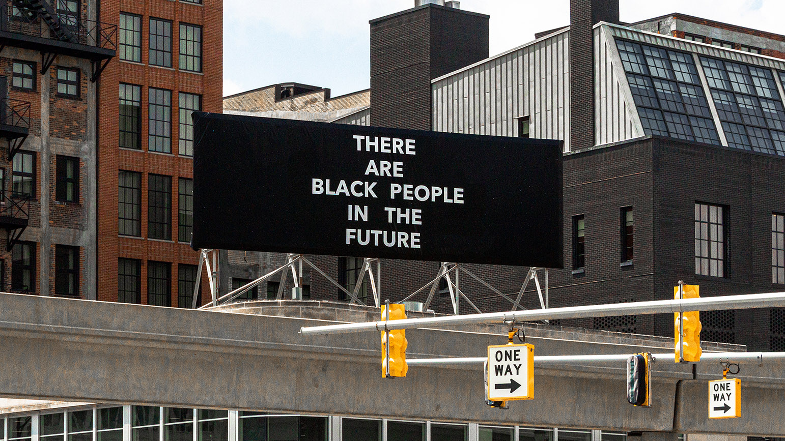 "Photograph of a black billboard with the words ""There Are Black People in the Future"" written in white capital letters"