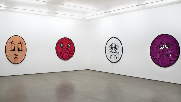 Gallery installation view with four large pain-scale faces constructed from fabric