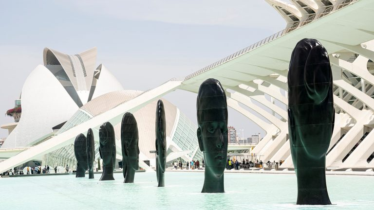 Seven large flat sculptures of serene faces installed in a shallow pool of water
