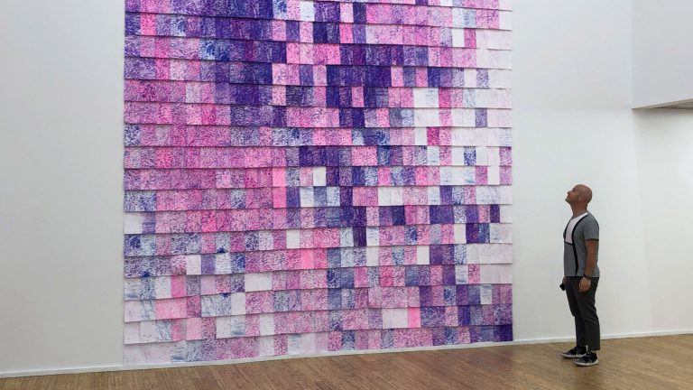Photograph of a man looking at a large installation of blue and pink sheets of rubbings of road texture