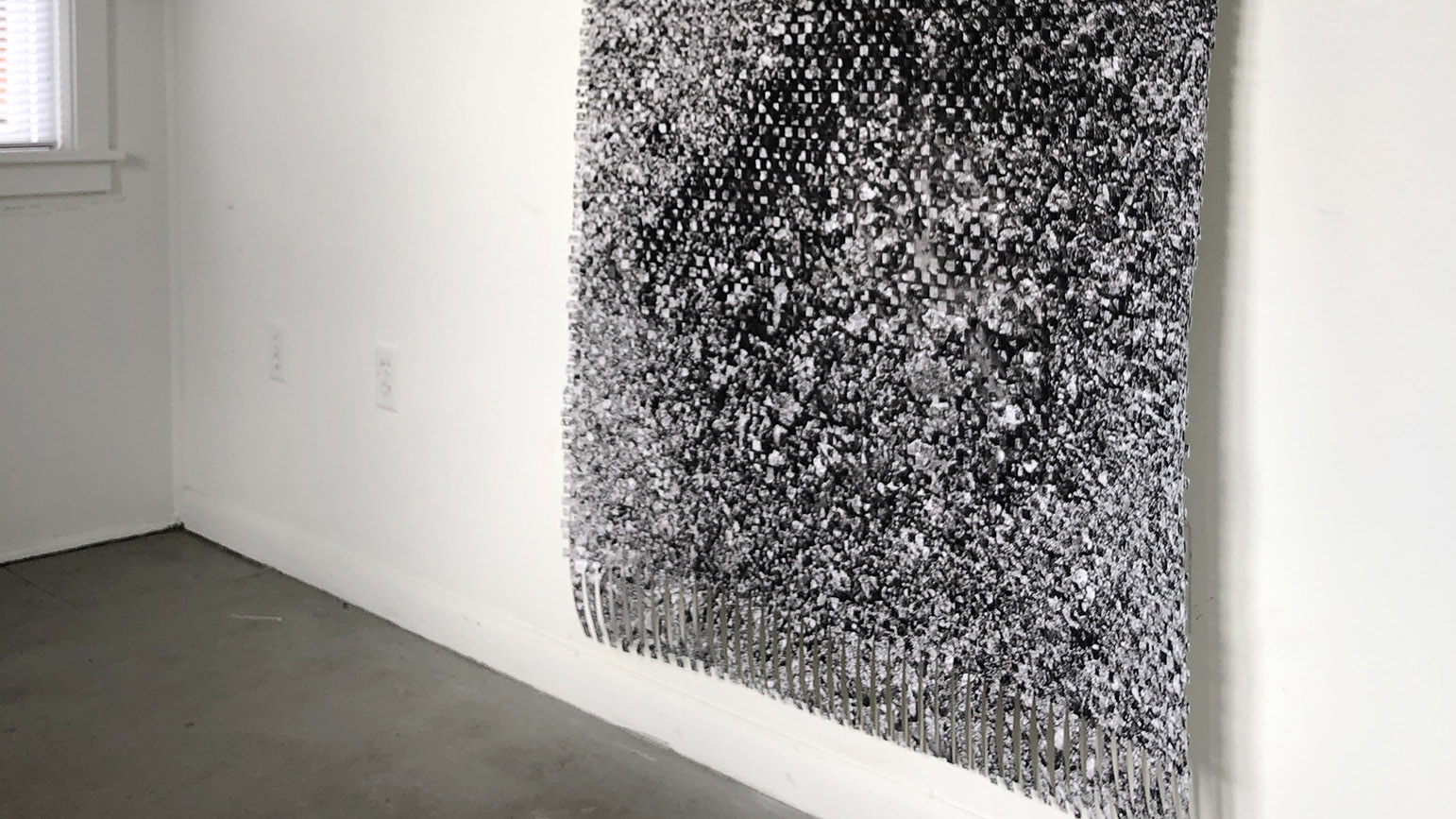Photograph of a paper weaving of road texture installed in a gallery