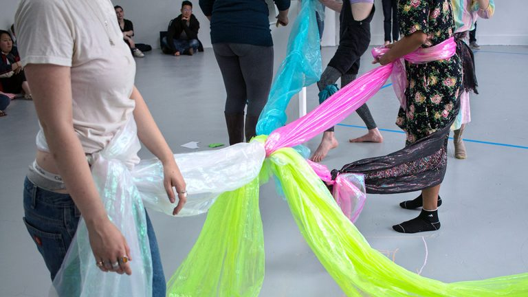A group of people connected at the waste by brightly colored fabric