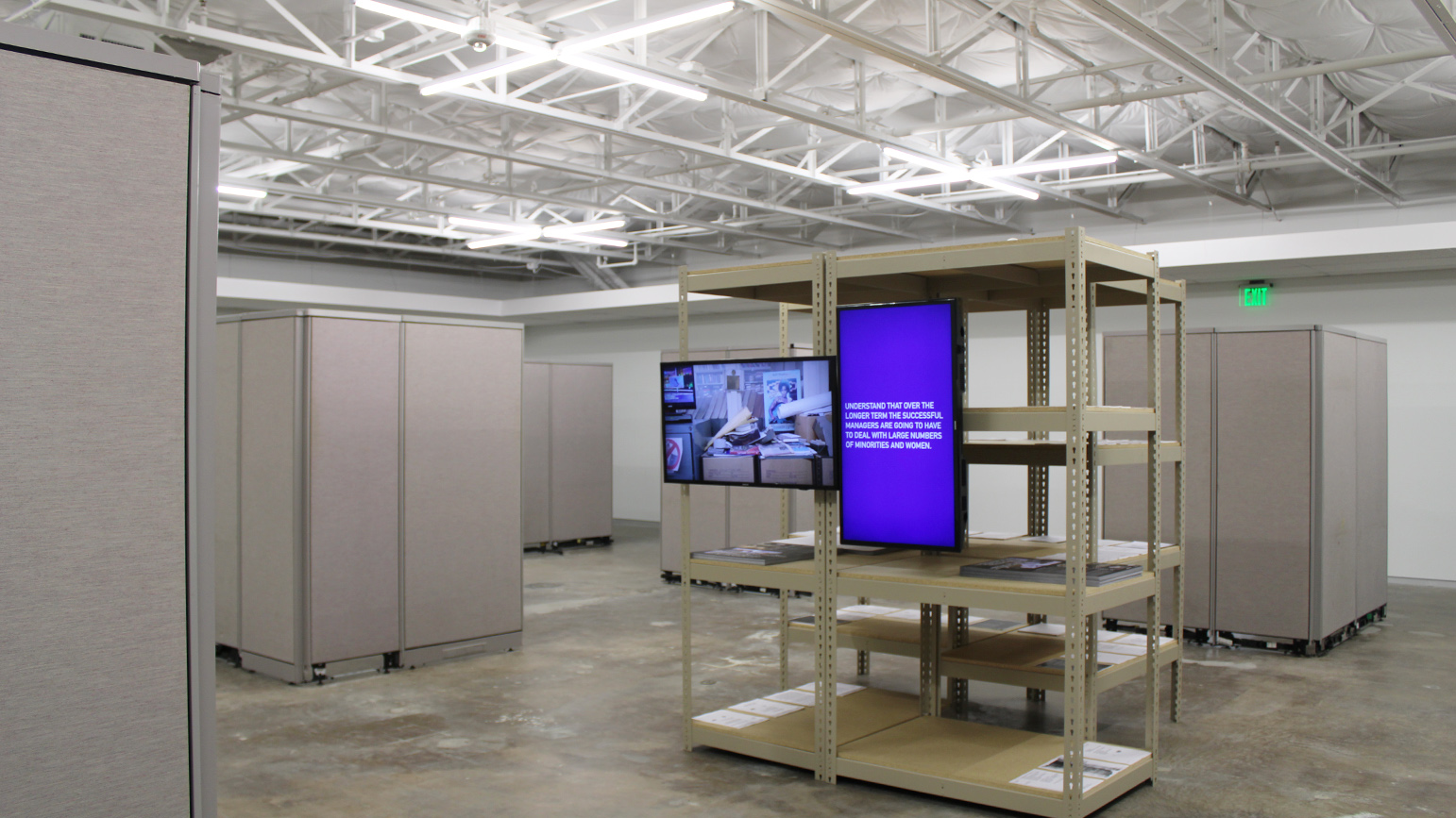 Gallery installation with cubicles, metal shelving, and two flat screen televisions