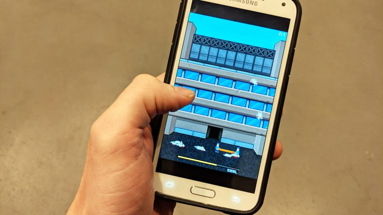 "Photograph of a hand holding a smartphone playing ""Phone Story"""