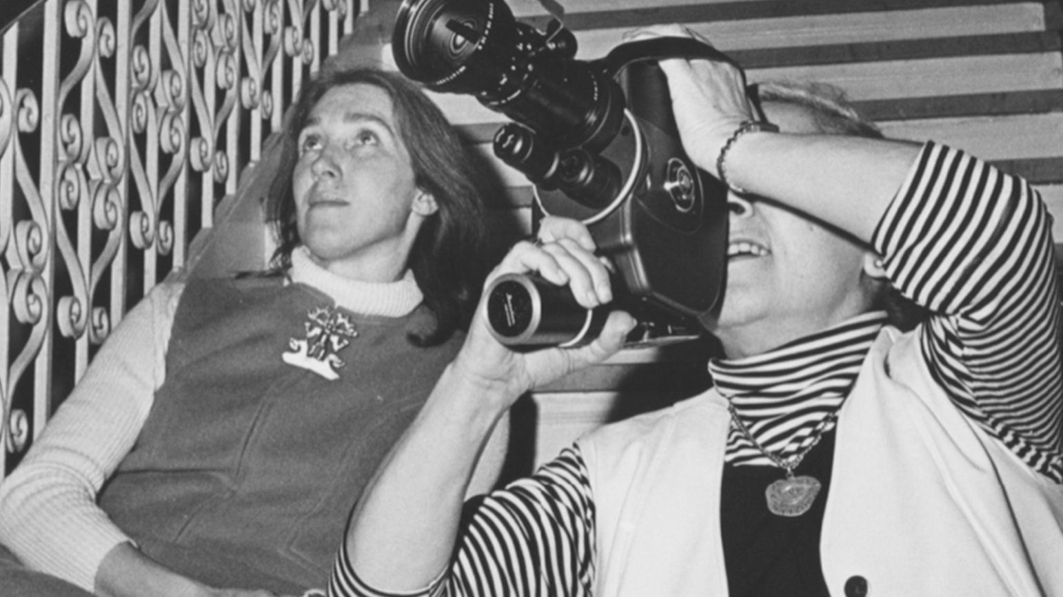 Black and white photograph of two women seated, one looking through a video camera