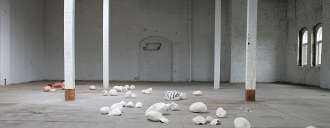 Small ceramic sculptures installed on the floor of an old industrial space
