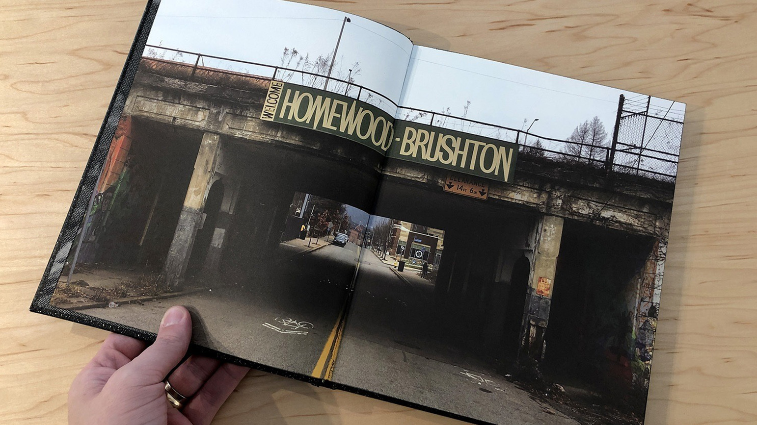 "Open book with a two-page photograph spread showing an overpass with a sign with the words ""Homewood Brushton"""