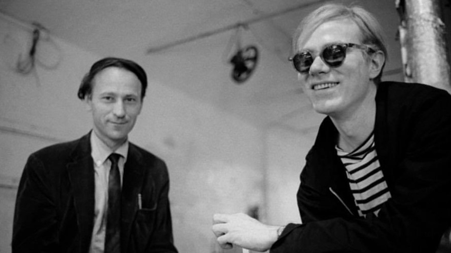 Black and white photograph of two men sitting: Jonas Mekas and Andy Warhol