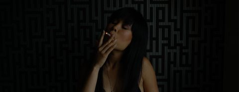 Woman smoking in a dark room