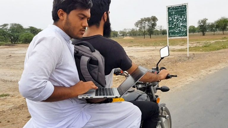 Photograph of two men on a motorcycle, one holding a laptop