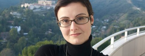 Headshot of Maria Elena Versari with a hilly cityscape in the background