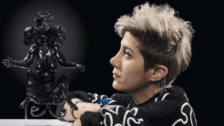 Headshot of Morehshin Allahyari looking at a black three-headed sculpture on a tabletop