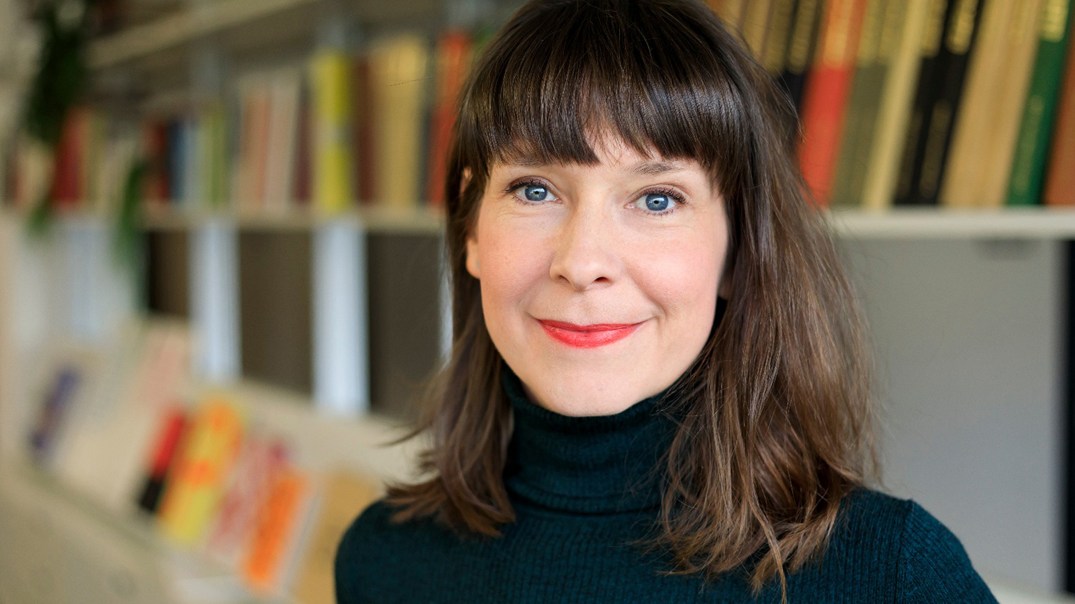 Headshot of a woman with a bookshelf in the background