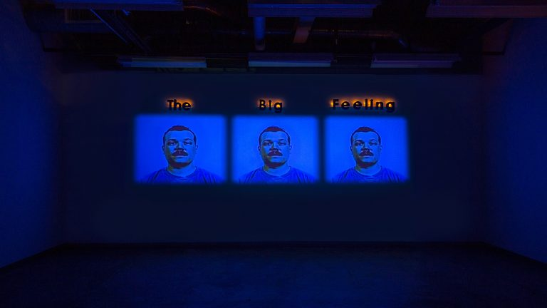 "Three video projections showing the identical face with the works ""The Big Feeling"" above the projections"